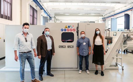 A group of four people wearing face masks standing next to new Carlo Salvi machine
